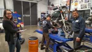 Monica from Inspire and Marc Beyer from OCD Custom Cycles & Auto Repair watching Alexis Flores working.
