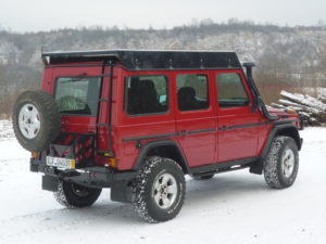 Red G-Wagen with rear swinging tire mount and fuel tank, side rails, snorkel, and roof rack.